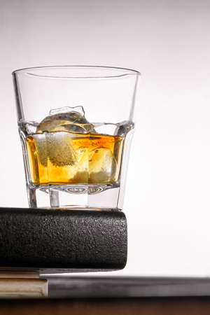 a glass of whiskey with ice stands on the corner of the bar counter on a light gray background. close up, bot view, copy space. vertical orientation