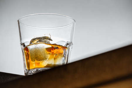 a glass of whiskey with ice stands on the corner of the bar counter on a light gray background. close up, bot view, copy space. horizontal orientation Banco de Imagens