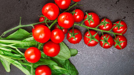 two ripe cherry tomato branch with spinach on a black embossed table. copy space, top view, flat lay Standard-Bild