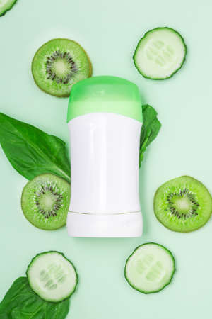 white jar antiperspirant, deodorant with a green lid with slices of cucumbers, kiwi and leaves freshness on a light mint background. close up, copy space, mock up
