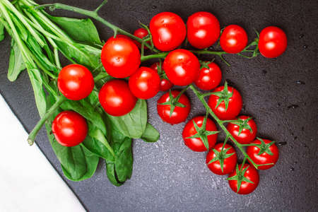 two ripe branches of cherry tomatoes and a white linen towel with spinach on a black embossed table. copy space, top view, flat lay, horizontal orientation Zdjęcie Seryjne