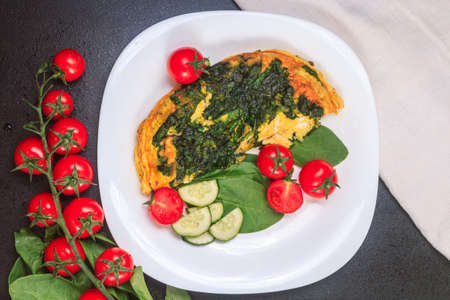 fried eggs with spinach and tomatoes, cucumbers on a white large plate on a black embossed table. top view, copy space