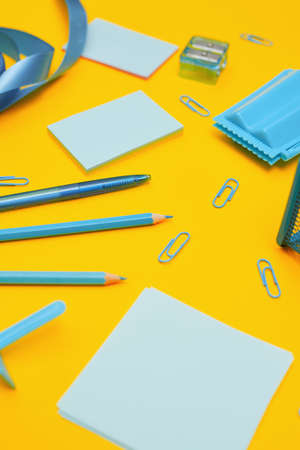 Minimalism, Back to school concept, blue school supplies on yellow background,copy space
