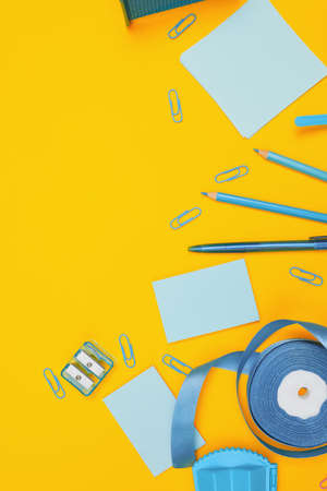 Minimalism, Back to school concept, blue school supplies on yellow background, flat lay copy space