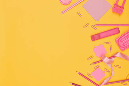 Minimalism, Back to school concept, Pink school supplies on yellow background, flat lay copy space