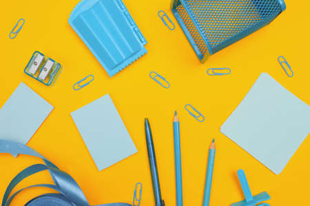 Minimalism, Back to school concept, blue school supplies on yellow background, with