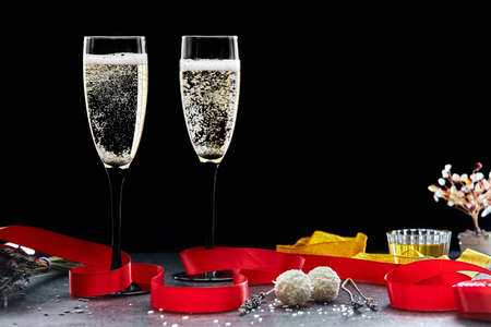 Two glasses of sizzling champagne with a red ribbon dark background, copy space