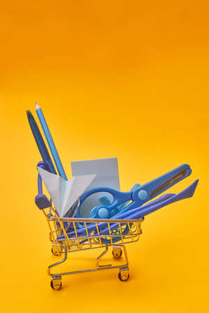 minimalism shopping cart and stationery on yellow background, school, university, copy space one
