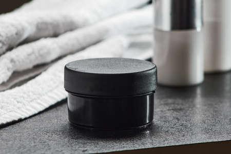 cosmetic black jar on a black table hair gel, bathroom .mocap, close up, copy space horizontal orientation