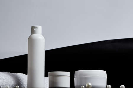white cosmetic jars for the bath a long tube of pearl towel on a gray and black background. copy space. mockup. bot view