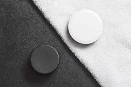 cosmetic black jar on a black table white cosmetic jar on a white towel .mocap, flat lay, top view, close up, copy space horizontal orientation