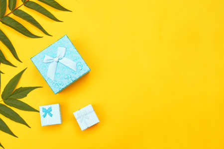 minimalism blue boxes with gifts on a yellow background