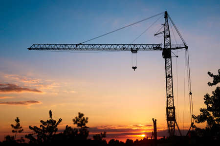 silhouette tower construction crane on sunset background, copy