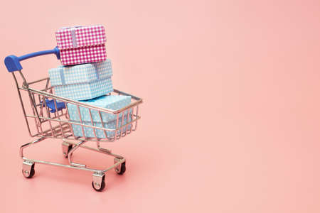 concept black friday, gift boxes with shopping cart on pink pastel background, copy space, flatlay