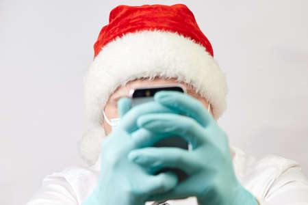 coronavirus concept, man in santa hat and medical mask with phone on white background Stock Photo