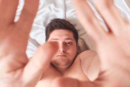 man on white bed wakes up stretching High Key, closeup 版權商用圖片