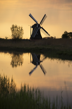 silhouette of a mill and its reflection in the water at sunrise