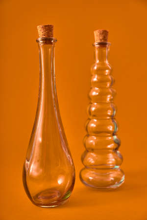 Empty glass bottle with original shapes on a solid neutral colored background. Studio lighting. Concept for advertising with space for sign or edition.