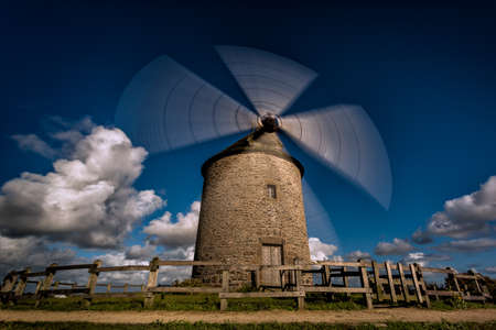 idyllic windmill in the Normandy region of france with moving blades and clouds in the background