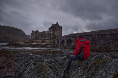 Historic castle and famous for its proximity to the Iska de Skye. Cold environment at low tide with man sitting