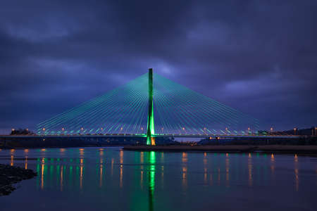 Modern line bridge illuminated with green lights for St. PAtricK in Waterford Ireland. Overnight.