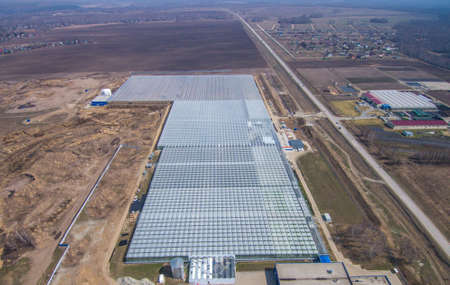 row of glass greenhouses for vegetable production. aerial photo Banque d'images