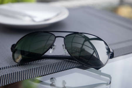 A reflective sunglasses lying on a table
