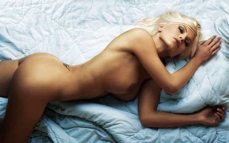 lying attractive naked blond girl in bed Stock Photo