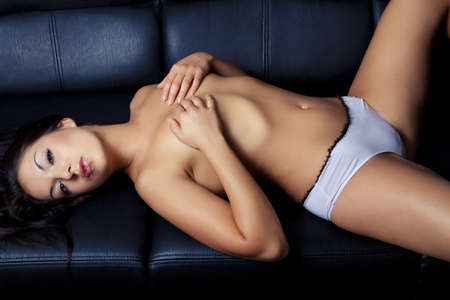 young girl nude: sexy beautiful young girl lying on black sofa Stock Photo