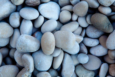 Naturally polished white rock pebbles background on beach photo