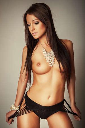 seins nus: jolie jeune fille brune topless en lingerie noire Banque d'images