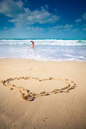 heart in sand: the heart on beach sand, blue sea Stock Photo