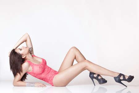 ropa interior femenina: chica por la atractiva en ropa interior rosada de encaje en el piso