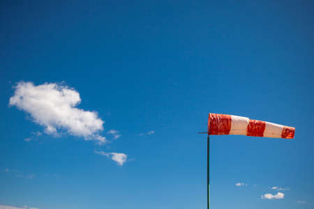 blue cloudy sky: red wind vane against a blue cloudy sky Stock Photo