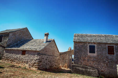 quaint: old stone rustic house and blue summer sky