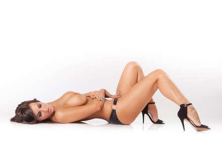 glamour chica atractiva morena con grandes pechos acostado en el piso blanco Foto de archivo