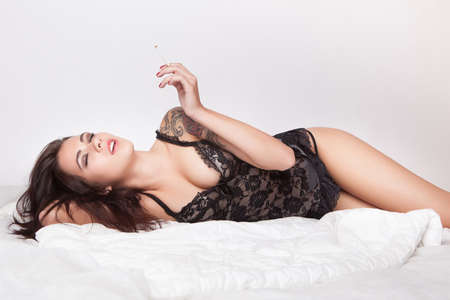 sexy funny: attractive tattoo pin up girl with cigarette in white bed