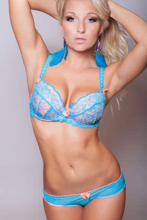 beaux seins: attrayante jeune fille blonde pose en lingerie avec de gros seins