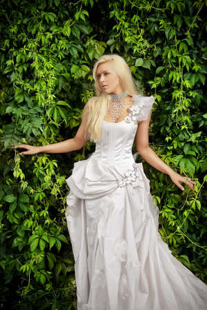 attractive blonde bride in luxury white clothes photo