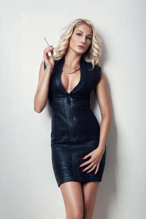 nude blonde: sexy blonde girl in black clothes with cigarette Stock Photo