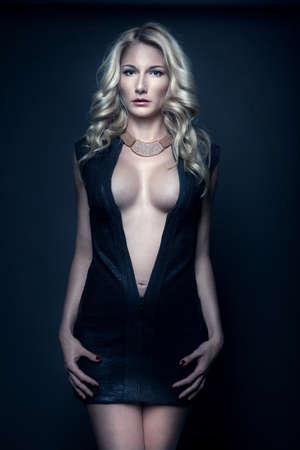 beaux seins: sexy jeune fille blonde dans des vêtements noirs avec de beaux seins