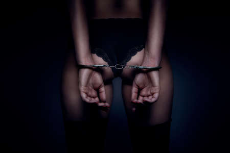 erotic: attractive girl back and hand with handcuffs, dark scene Stock Photo