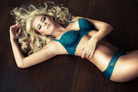 girl boobs: attractive slim blonde girl in sexy lingerie laying on wooden floor Stock Photo