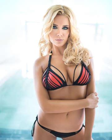 big boobs: atractiva hermosa chica rubia en traje de baño negro y rojo