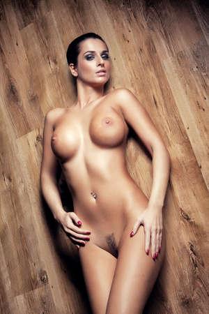 seni: nudi attraente ragazza sexy con grossi seni sul pavimento di legno