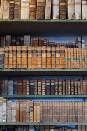 antique books: historic old books in ancient library, wooden bookshelf
