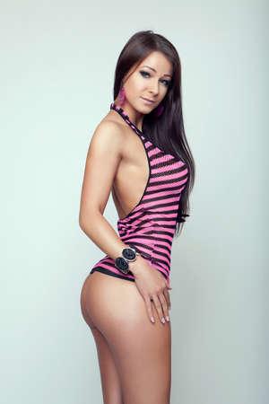 curvas: belleza morena chica sexy en mini tira de ropa de color rosa