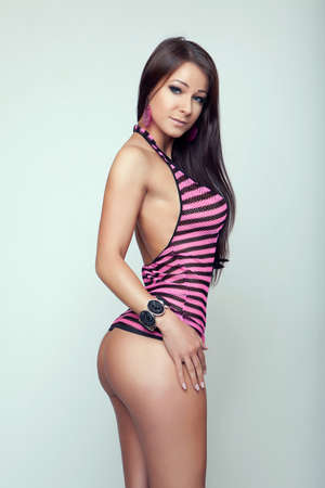 body curve: sexy beauty brunette girl in mini strip pink clothes