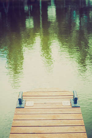 Wooden wharf and green blue water