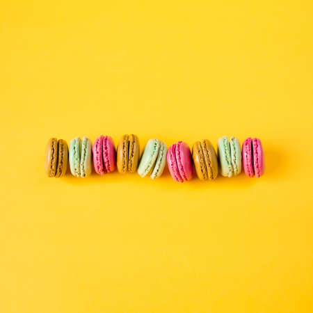 pink brown: pink, brown, orange and green macarons on yellow background Stock Photo